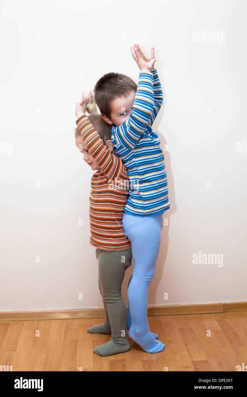 Dos hermanitos mostrando y comparando la altura del cuerpo Imagen De Stock