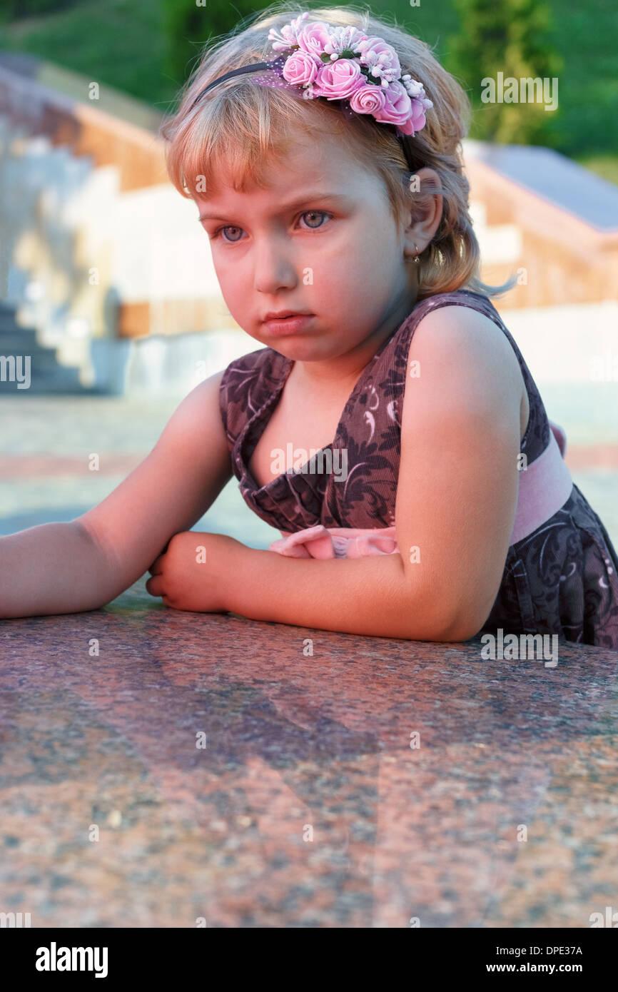 Retrato de la niña triste sobre el terraplén de granito. Imagen De Stock