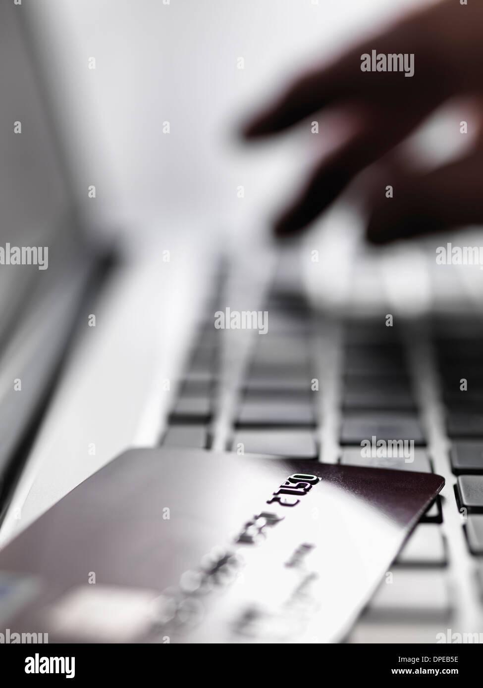 Tocar a mano los detalles de la cuenta en el ordenador portátil para ilustrar sus compras en internet y el Imagen De Stock
