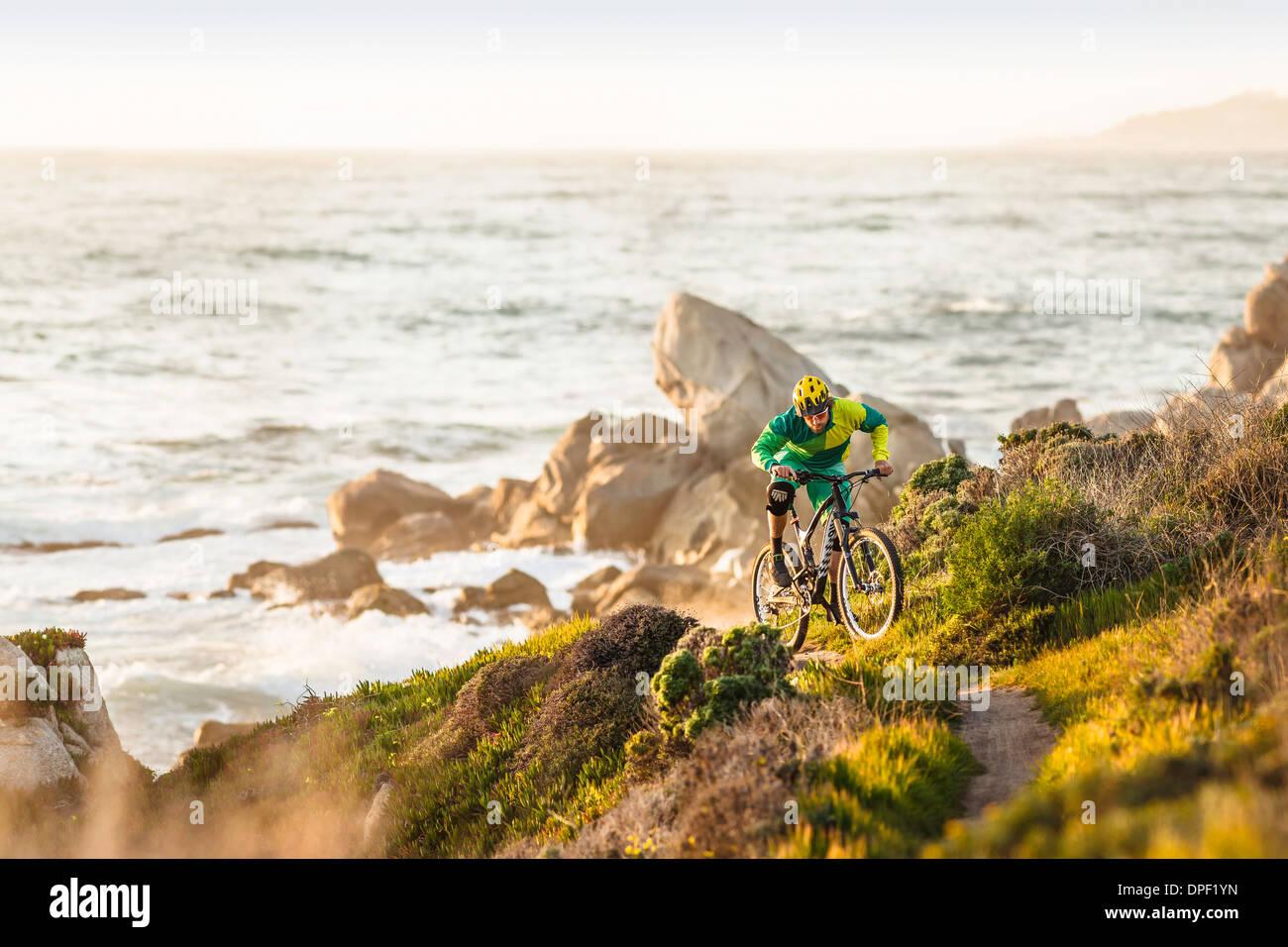 Ciclista de montaña sube la ruta costera, el área de la bahía de Monterey, California, EE.UU. Imagen De Stock