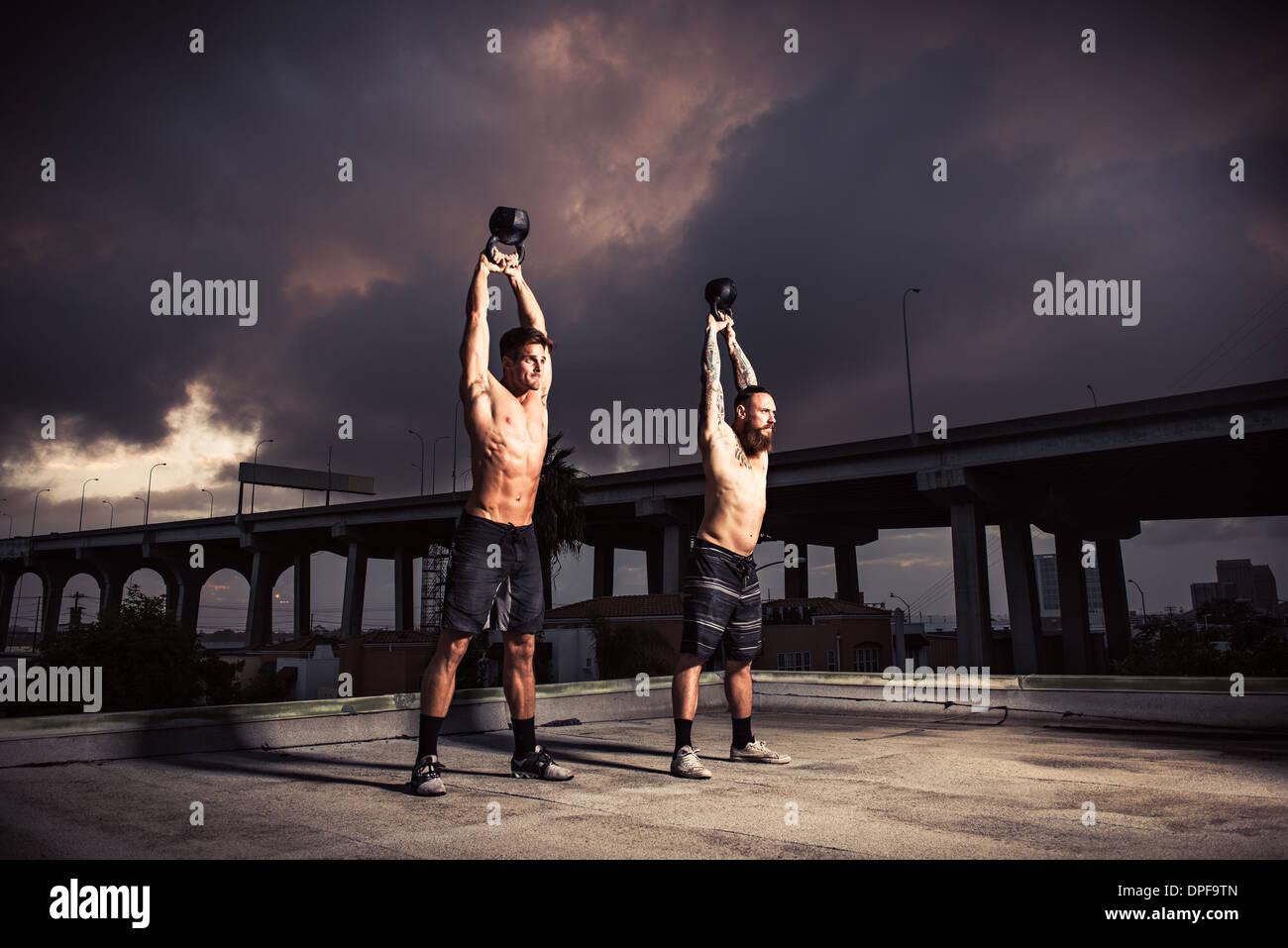 Dos hombres con entrenamiento en el gimnasio de la azotea kettlebells Foto de stock