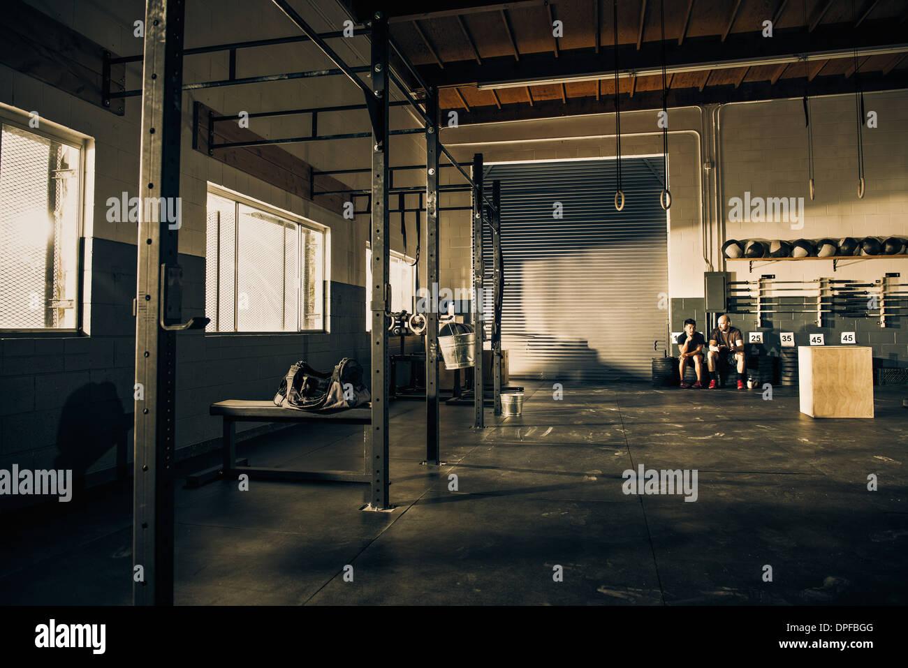 Dos hombres tomando un descanso del entrenamiento en el gimnasio Foto de stock