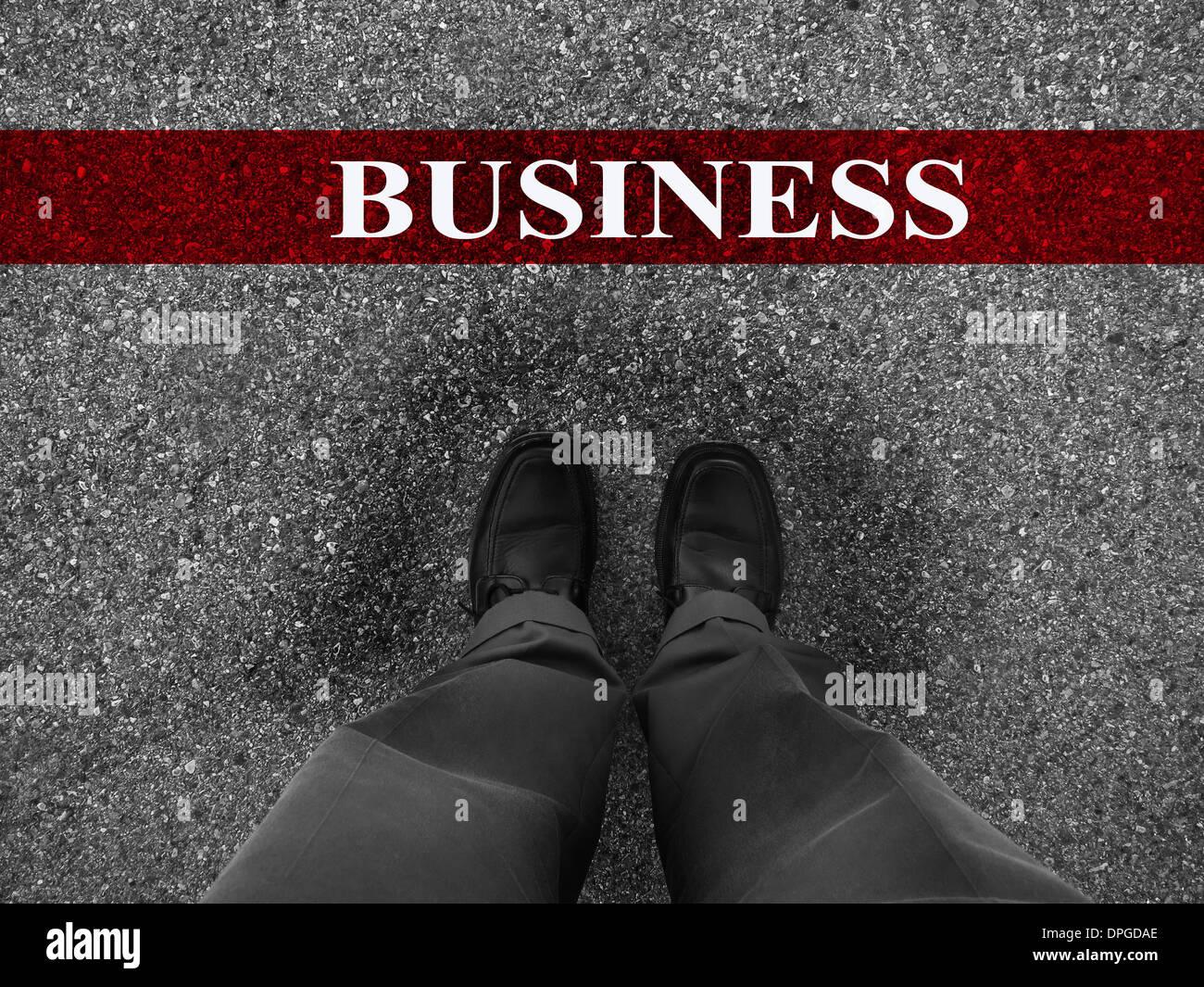 Empresario de pie sobre asfalto con motivación starting line palabra de negocio Imagen De Stock