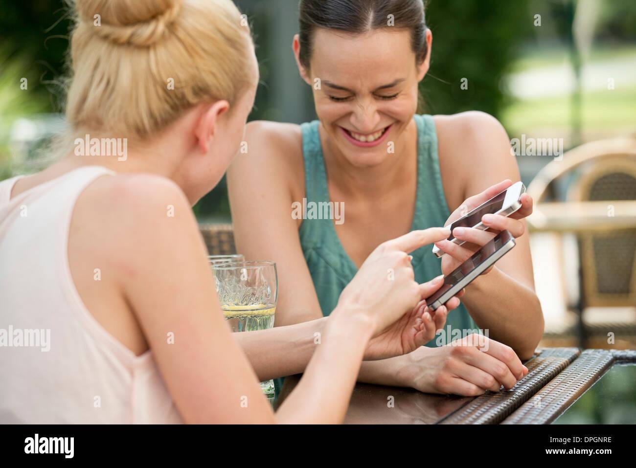 Los amigos comparten reír a través de los medios de comunicación social Imagen De Stock