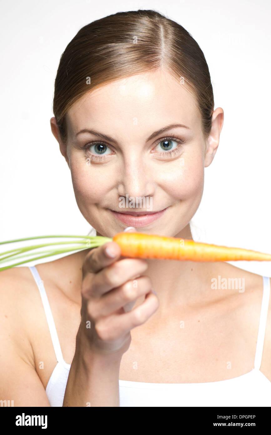 Mujer joven equilibrando la zanahoria en la mano, Retrato Imagen De Stock