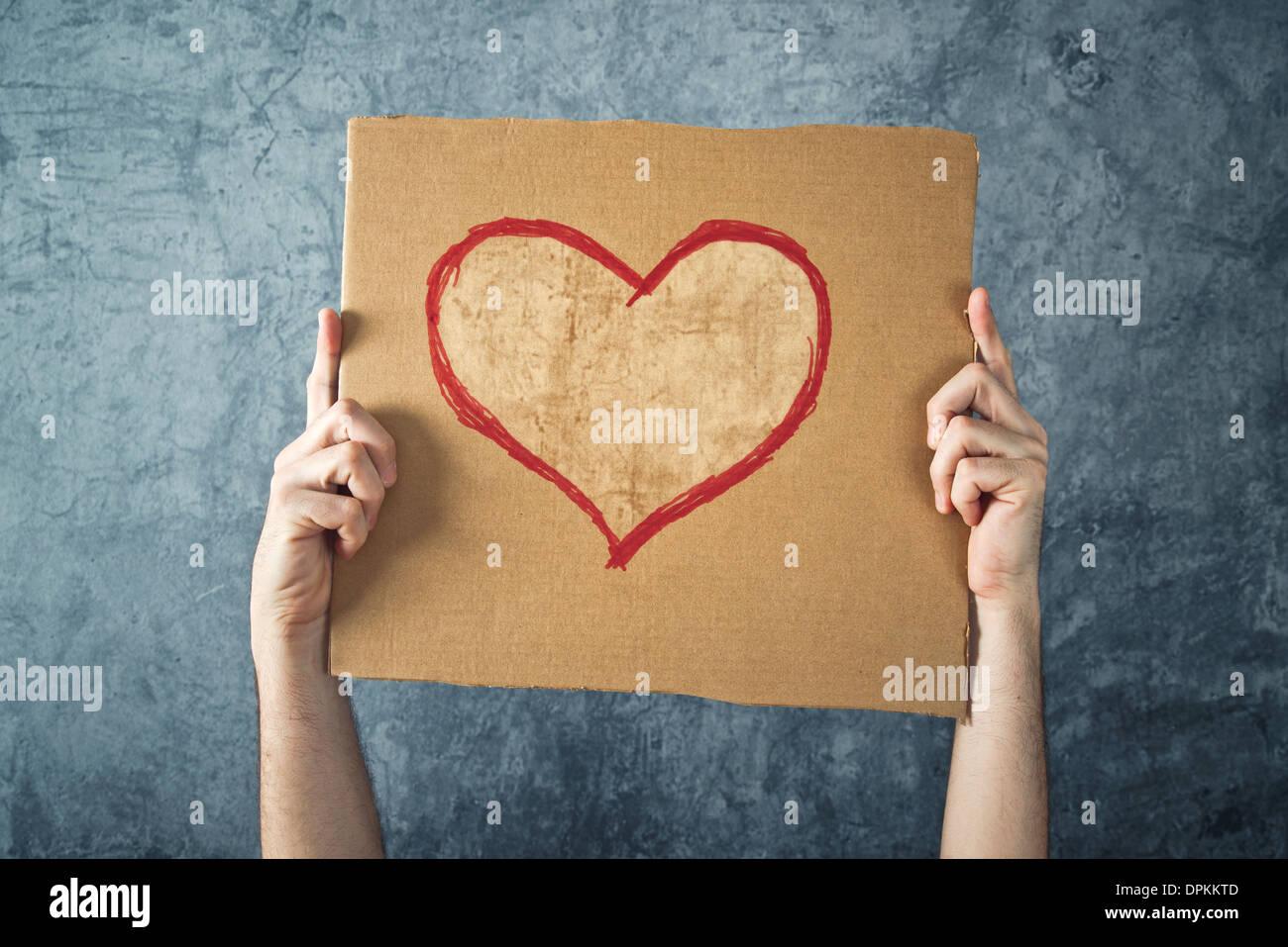 Hombre sujetando un cartón de papel con forma de corazón de San Valentín dibujo como imagen conceptual. Imagen De Stock