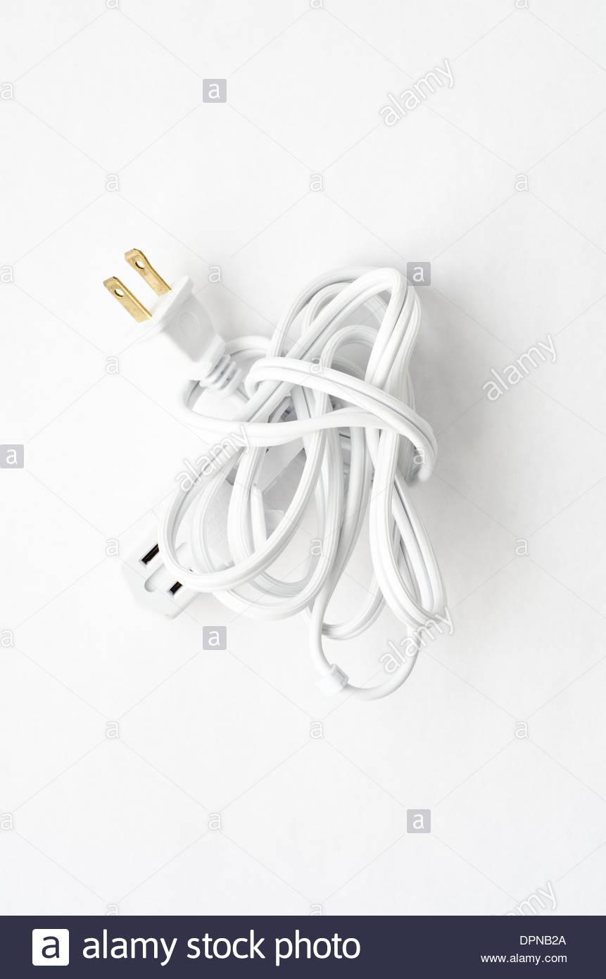 Paquete de cable alargador blanco atado en un nudo sobre fondo blanco. Imagen De Stock