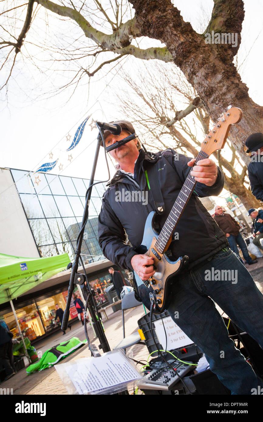 Músico callejero tocando la guitarra eléctrica y órgano de boca en el centro de la ciudad. Imagen De Stock