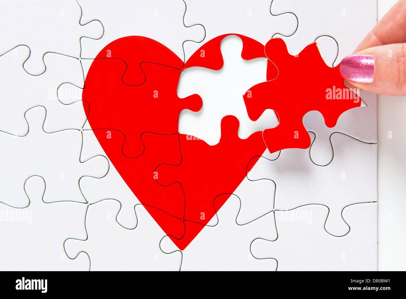 Una mujer poniendo la pieza faltante de un rompecabezas corazón rojo en su lugar Imagen De Stock
