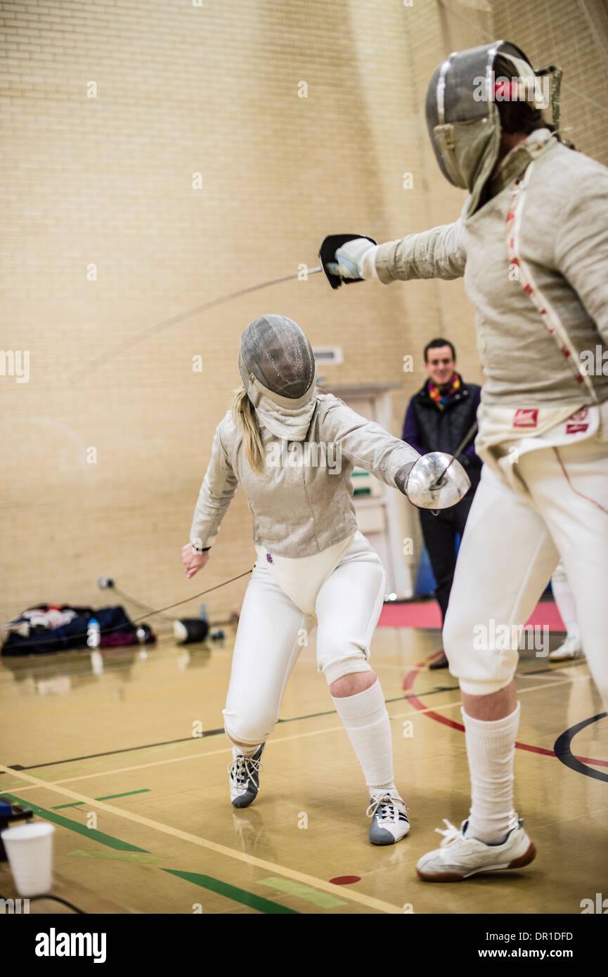 Dos mujeres estudiantes de la universidad de Aberystwyth esgrimidores compitiendo en esgrima, sable, estilo UK Imagen De Stock