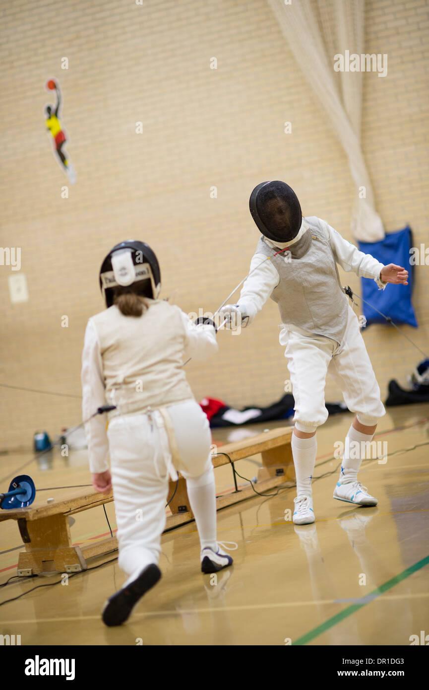Dos mujeres estudiantes de la universidad de Aberystwyth portando máscaras de seguridad compitiendo en esgrima (foil) , Reino Unido Imagen De Stock