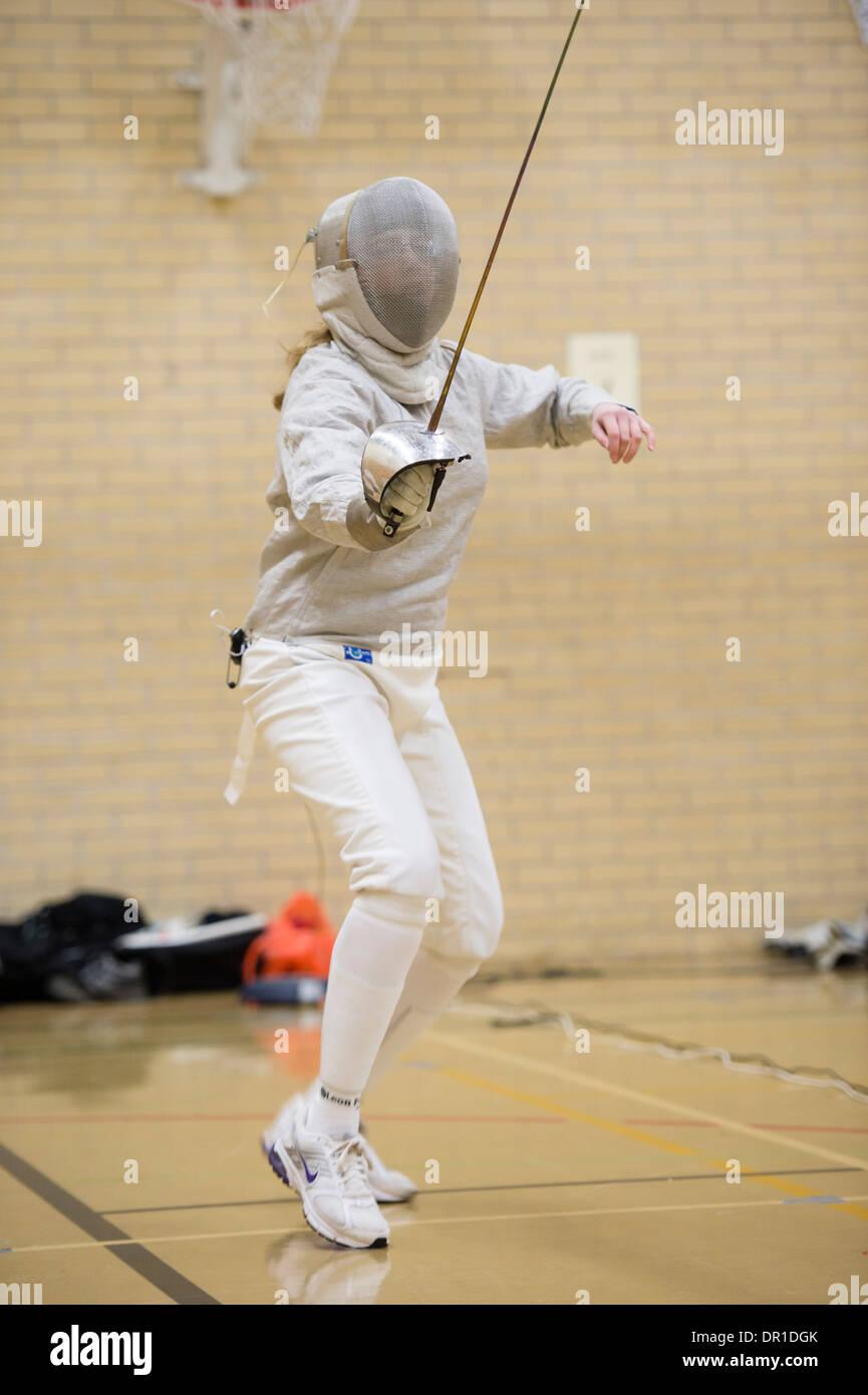 Una mujer Aberystwyth universidad estudiante vestido de máscara de seguridad compitiendo en sable de esgrima, estilo UK Imagen De Stock