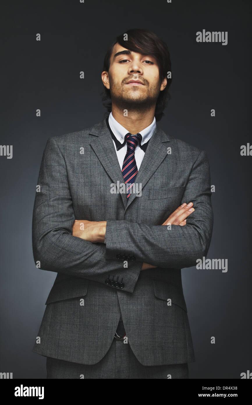 Retrato de joven negocio persona mirando con una actitud. Empresario con los brazos cruzados sobre fondo negro. Raza mixta Imagen De Stock