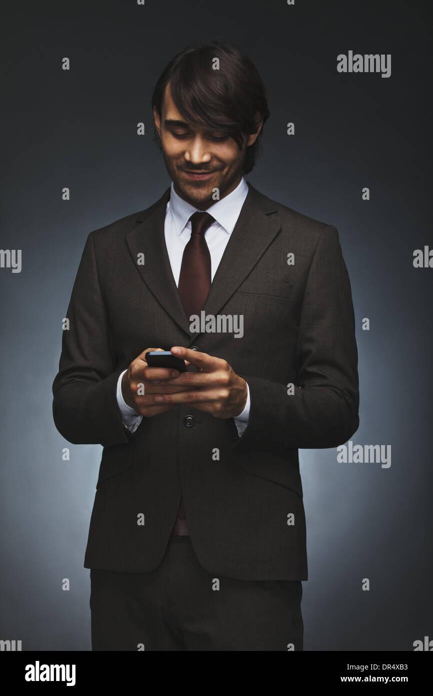 Feliz joven ejecutivo escribir mensajes de texto en su teléfono inteligente. Hermoso macho asociar la lectura de Foto de stock