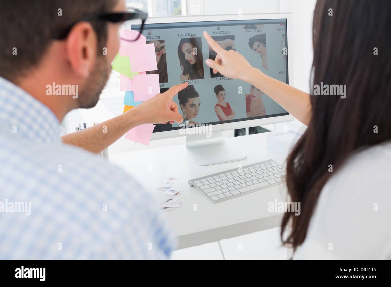 Vista trasera de editores fotográficos ocasionales trabajando en equipo Imagen De Stock