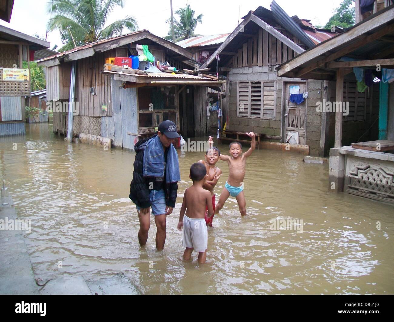 """Manila. 20 ene, 2014. Los residentes vadear una comunidad inundada en Compostela, ciudad en el sur de Filipinas"""" del valle de Compostela, 20 de enero de 2014. La Depresión Tropical Agaton, que causaron el sur y el centro de Filipinas, ha matado a 40 personas, la Dirección Nacional de Gestión y Reducción del Riesgo de Desastres (NDRRMC Consejo) divulgado el domingo. Crédito: FLIM/Xinhua/Alamy Live News Foto de stock"""