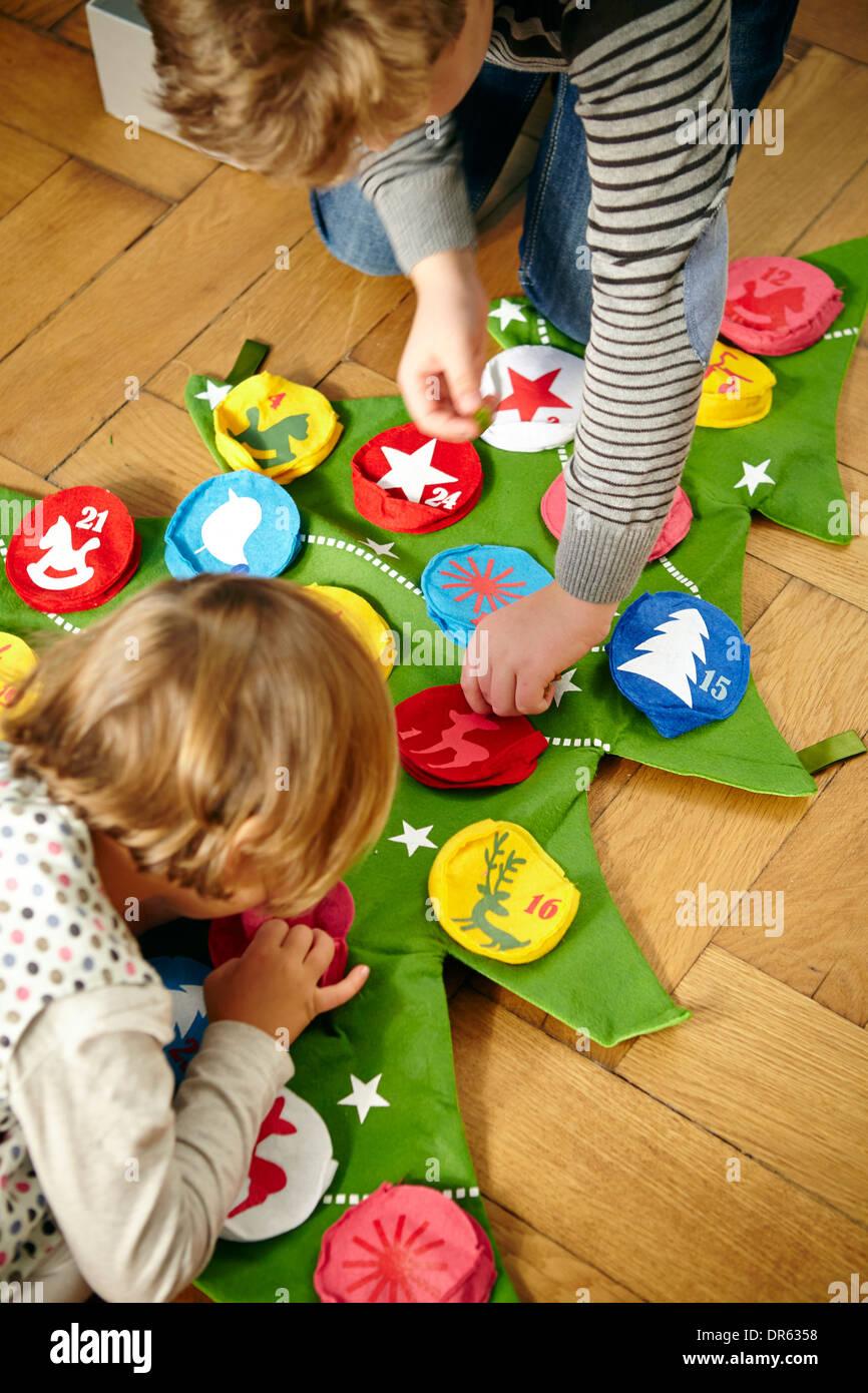 Los niños decorando calendario de Adviento, Munich, Baviera, Alemania Imagen De Stock