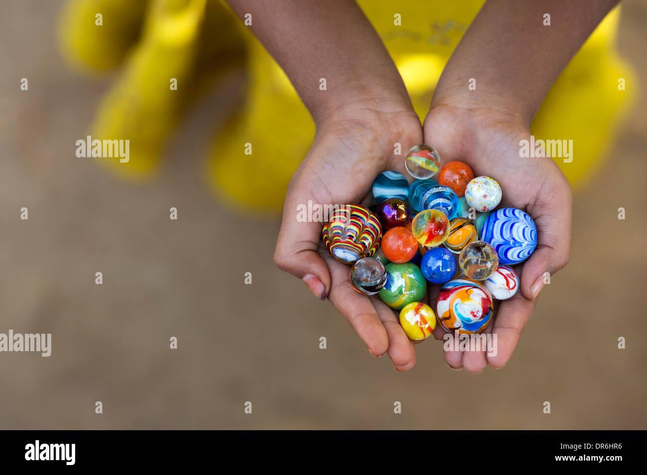Muchachas indias manos sosteniendo coloridos mármoles Imagen De Stock