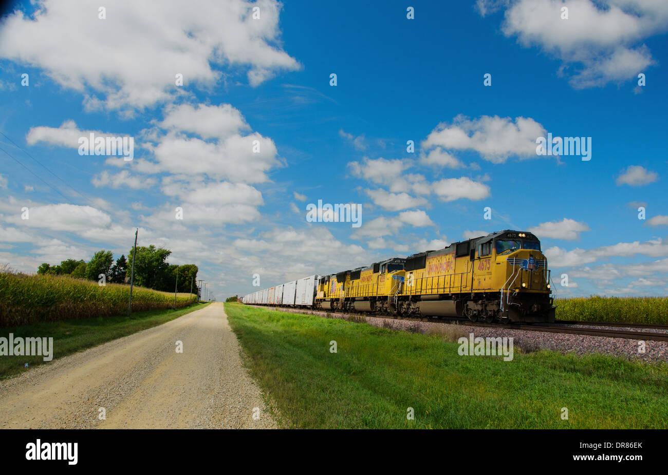 Lincoln Highway ripio junto a las vías del ferrocarril, donde el tren de Union Pacific está funcionando casi a Ashton, Illinois Imagen De Stock