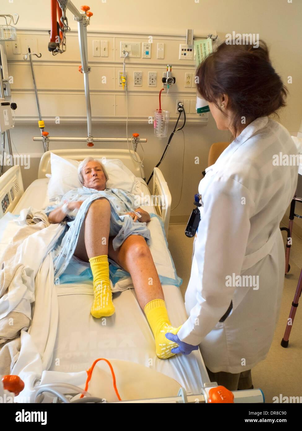 Un terapeuta ocupacional asiste a las mujeres recuperándose de la cirugía de reemplazo de cadera en un hospital del sur de California Imagen De Stock