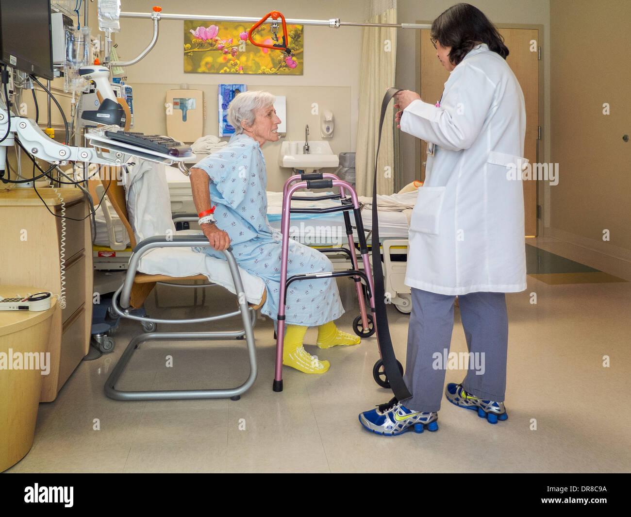 Un terapeuta ocupacional enseña una recuperación de una cirugía de reemplazo de cadera paciente en un hospital del sur de California para pararse. Imagen De Stock