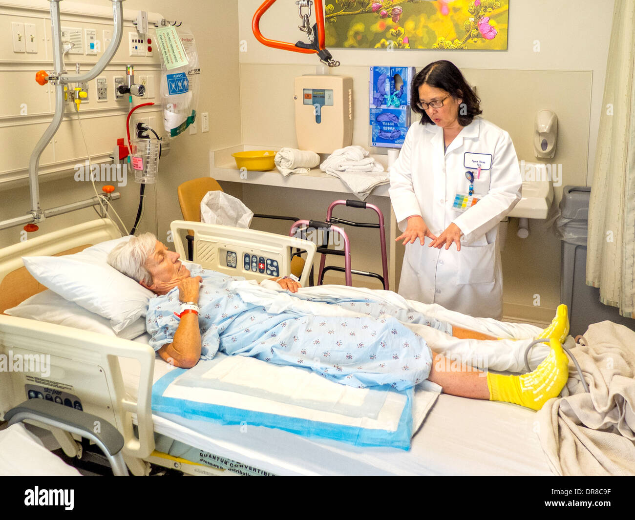 Un terapeuta ocupacional explica la postura correcta para una recuperación de una cirugía de reemplazo de cadera paciente. Imagen De Stock
