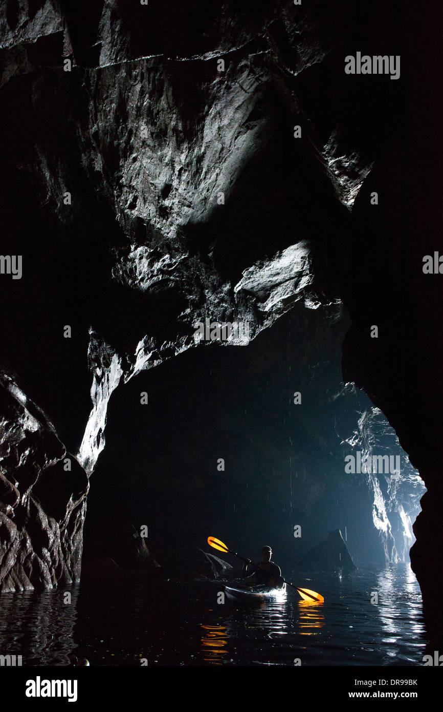Mar kayakista en una cueva debajo de los acantilados de Slieve League, Condado de Donegal, Irlanda. Foto de stock