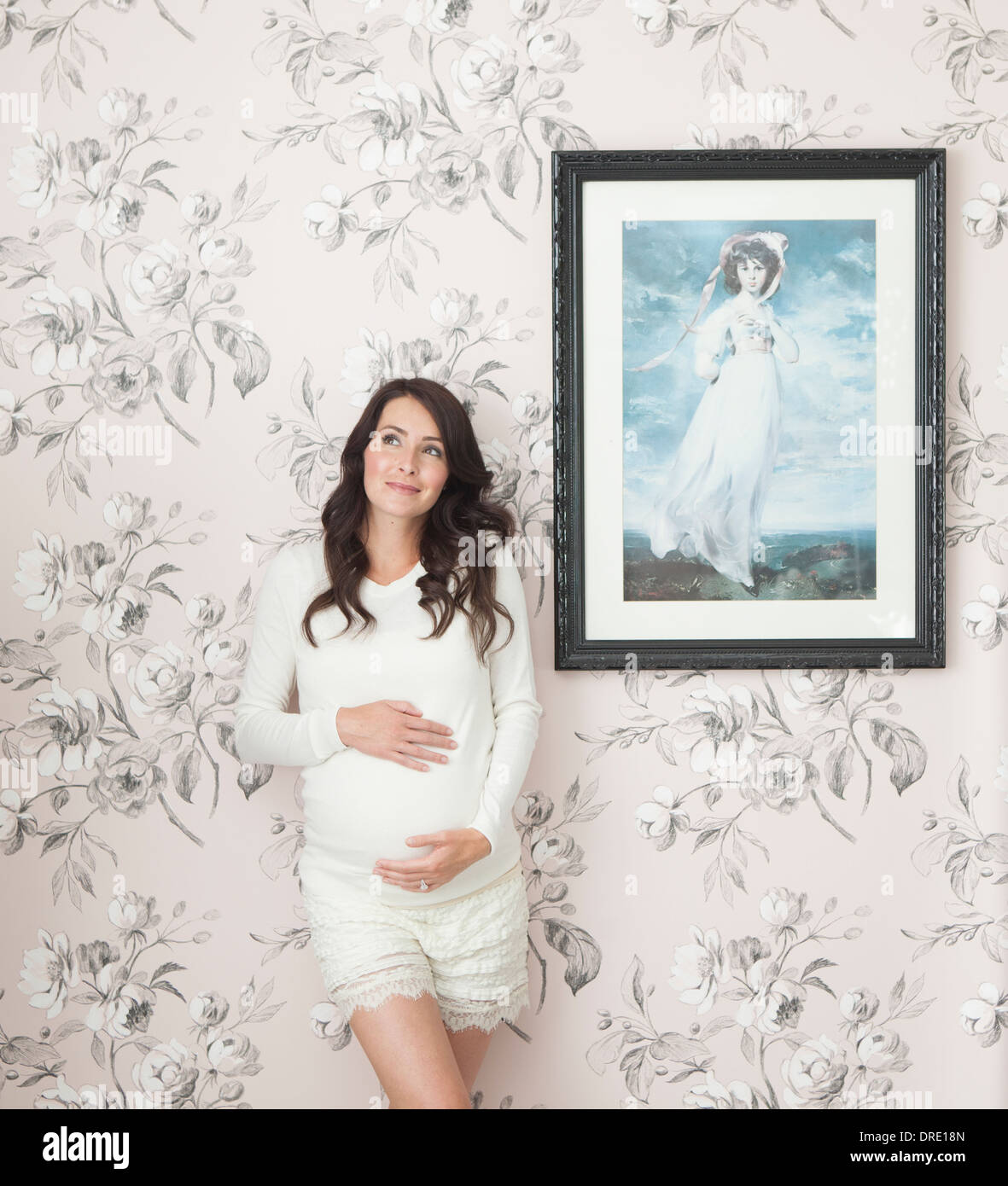 Mujer embarazada en frente de pared floral Imagen De Stock