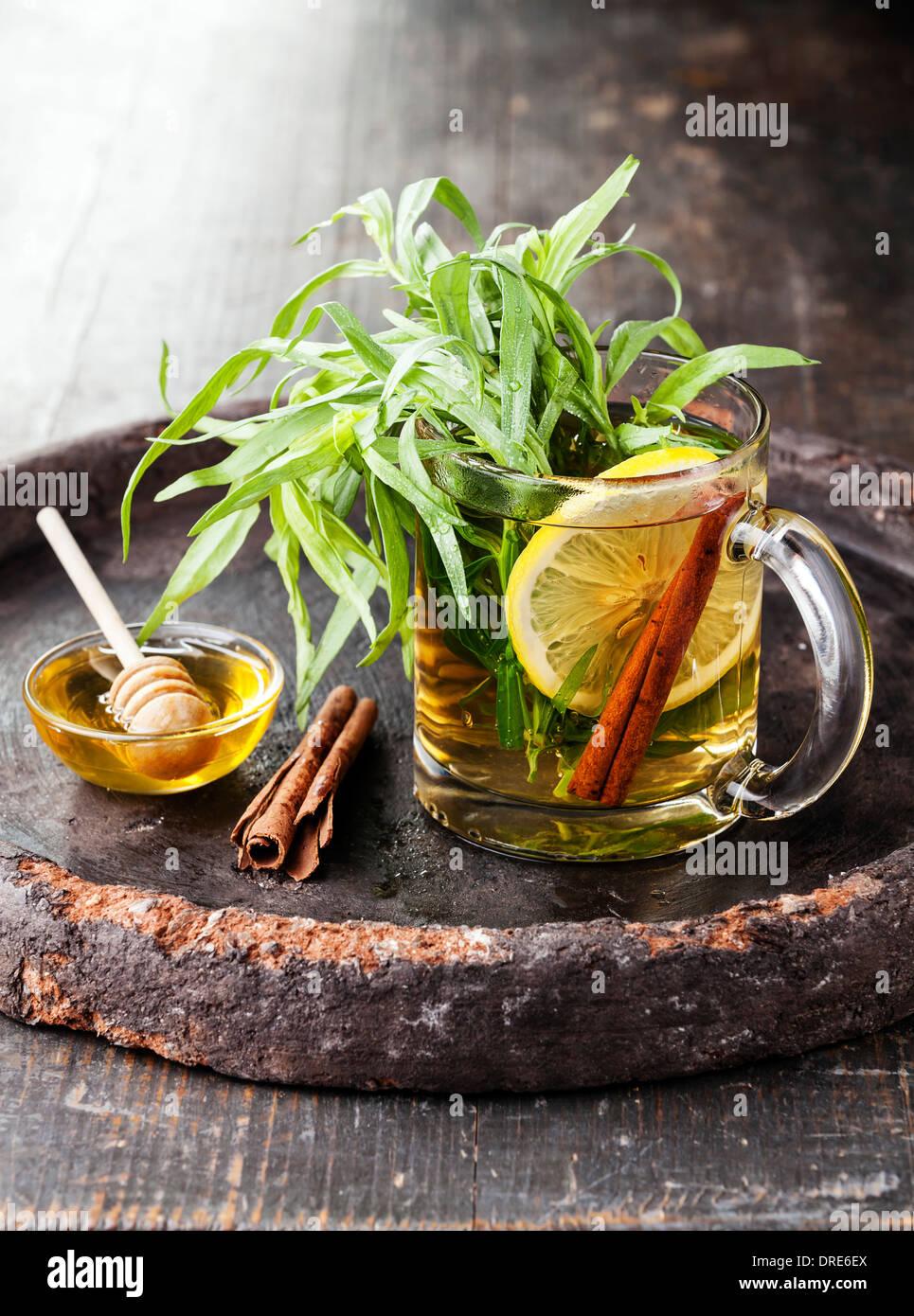 Estragón beber té caliente con miel, limón y canela sobre fondo oscuro Imagen De Stock