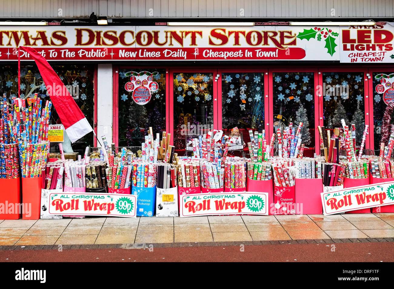 Rollos de papel de regalo de Navidad fuera de una tienda de descuento de Navidad. Imagen De Stock