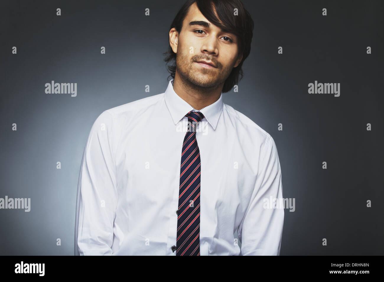 Retrato de joven apuesto macho ejecutivos de negocios, mirando a la cámara frente al fondo gris. Empresa joven asiática. Imagen De Stock