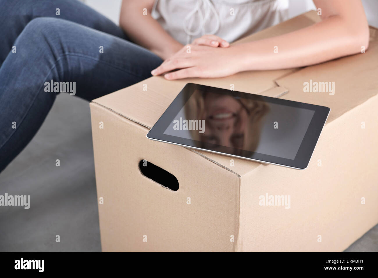 Mujer joven con caja de cartón y tablet pc Imagen De Stock
