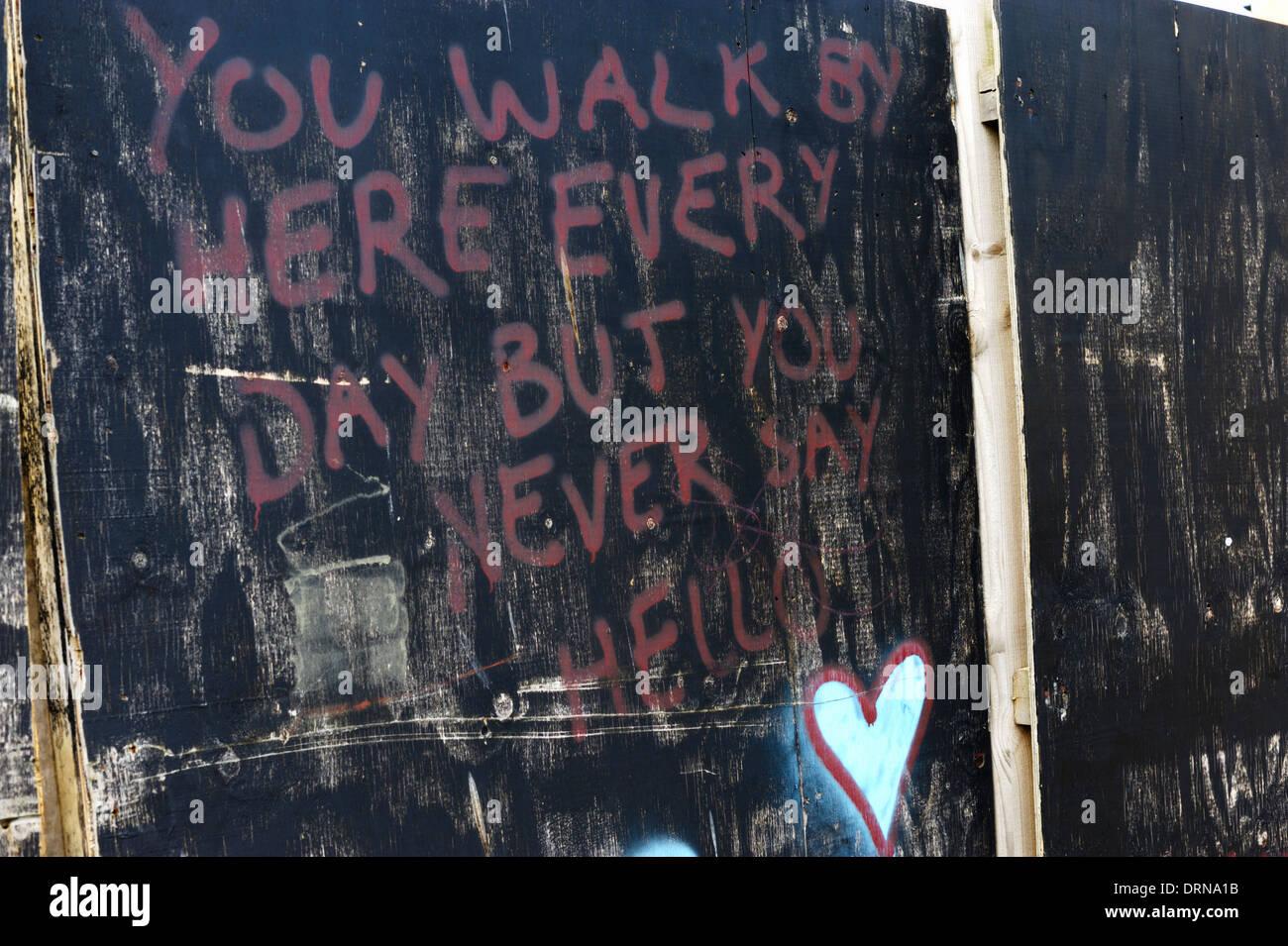 Graffiti, escritura roja sobre fondo negro ' usted camina por aquí cada día pero nunca dices hola', Wales, REINO UNIDO Imagen De Stock