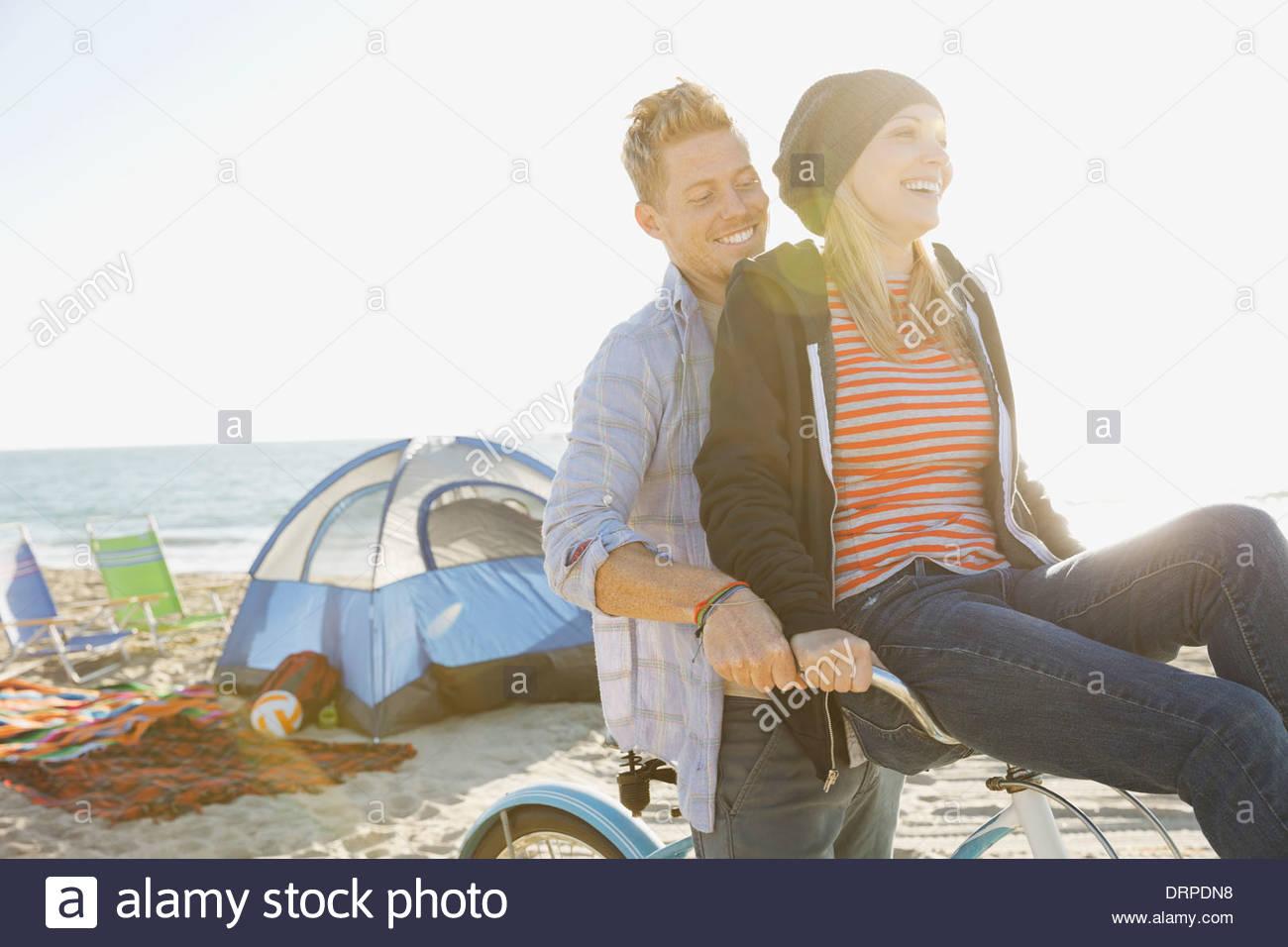 Pareja sonriente ciclismo en la playa Imagen De Stock