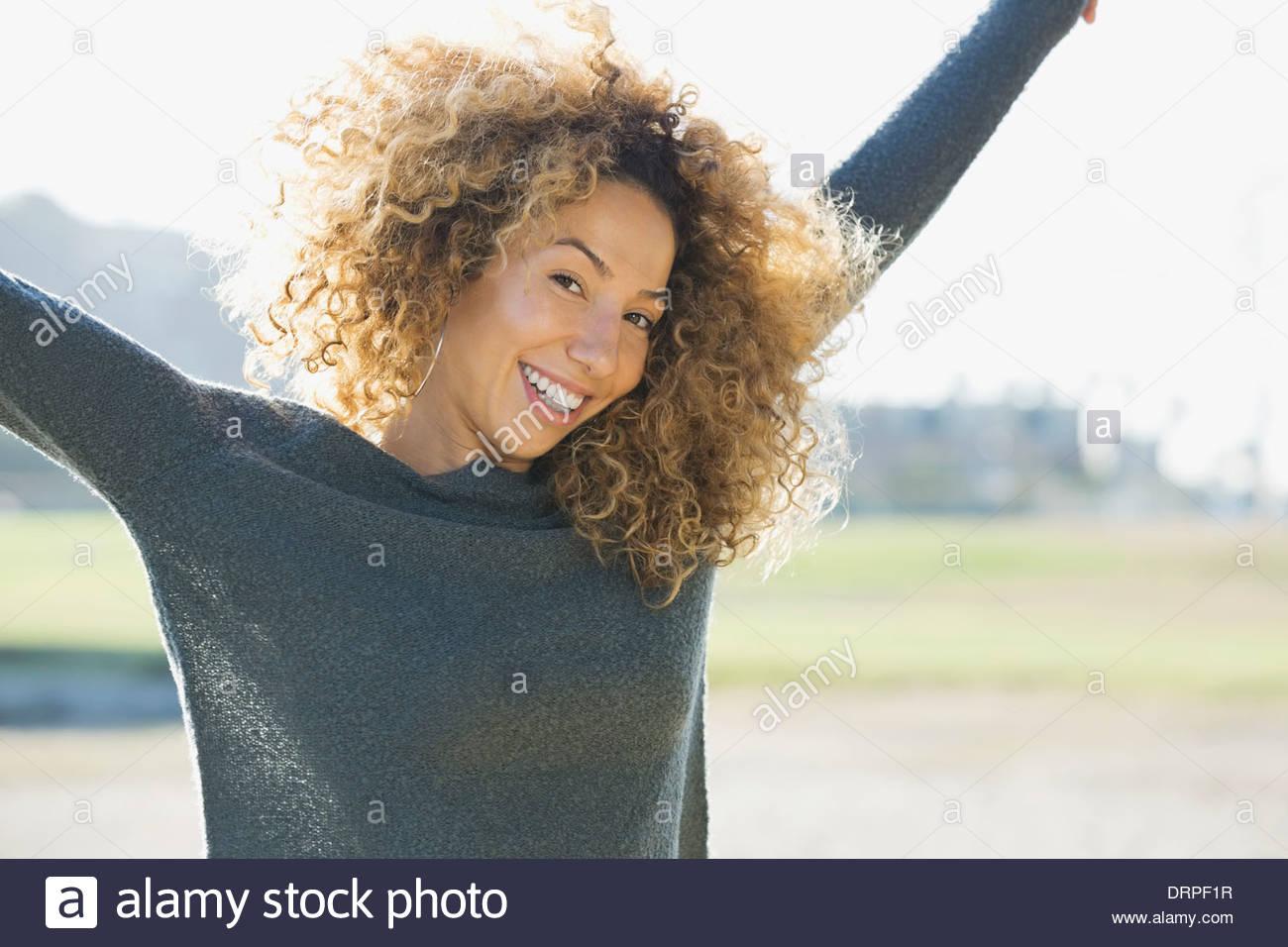 Retrato de mujer con los brazos levantados en el exterior Imagen De Stock