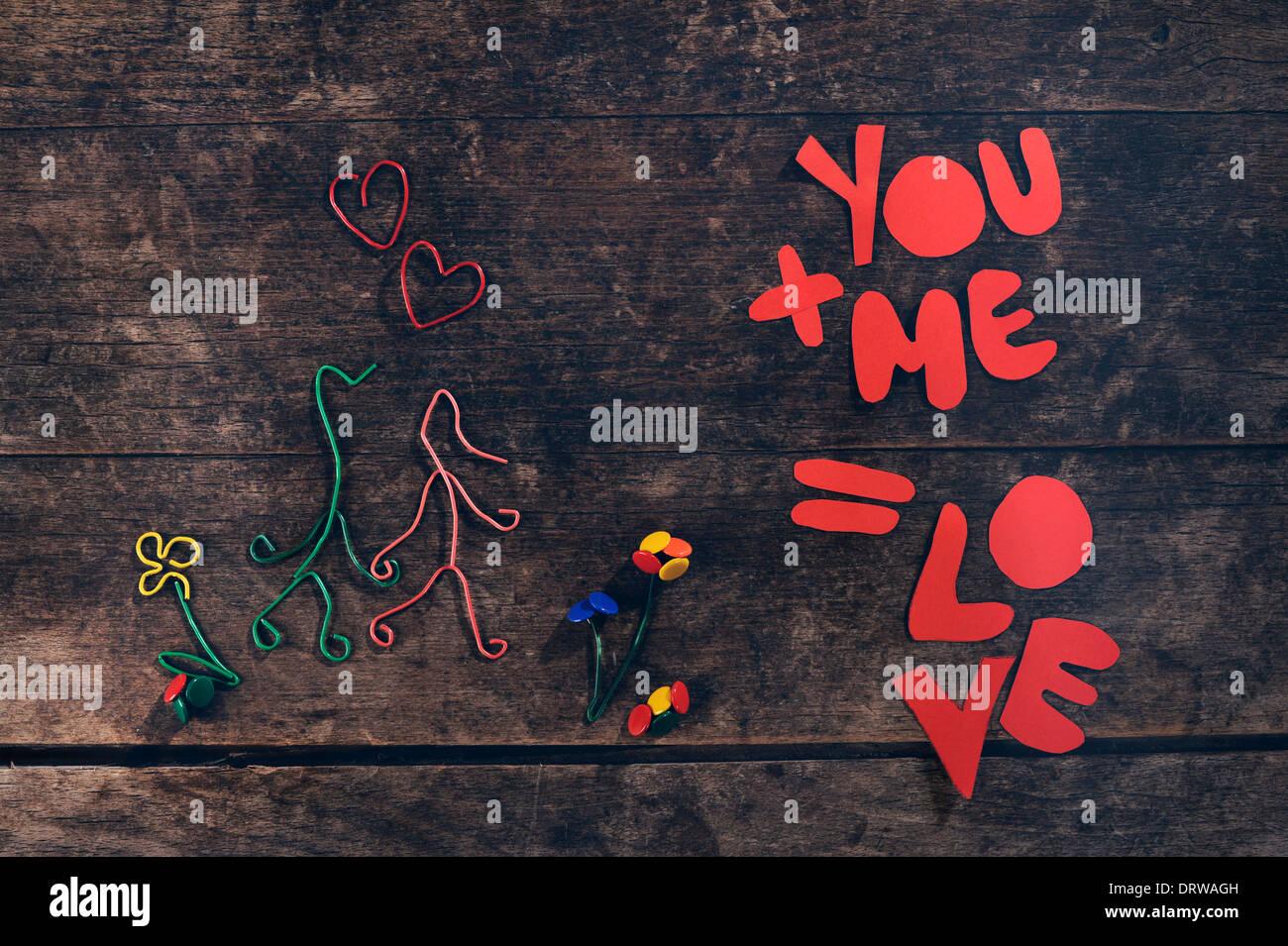 Mensaje de amor creativo. Par de manos hechas de papel y clips chinchetas sobre fondo de madera vintage. Foto de stock