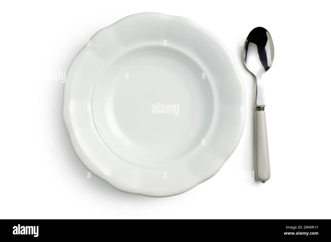 Vista superior de la placa de cerámica blanca con una cuchara sobre fondo blanco. Imagen De Stock