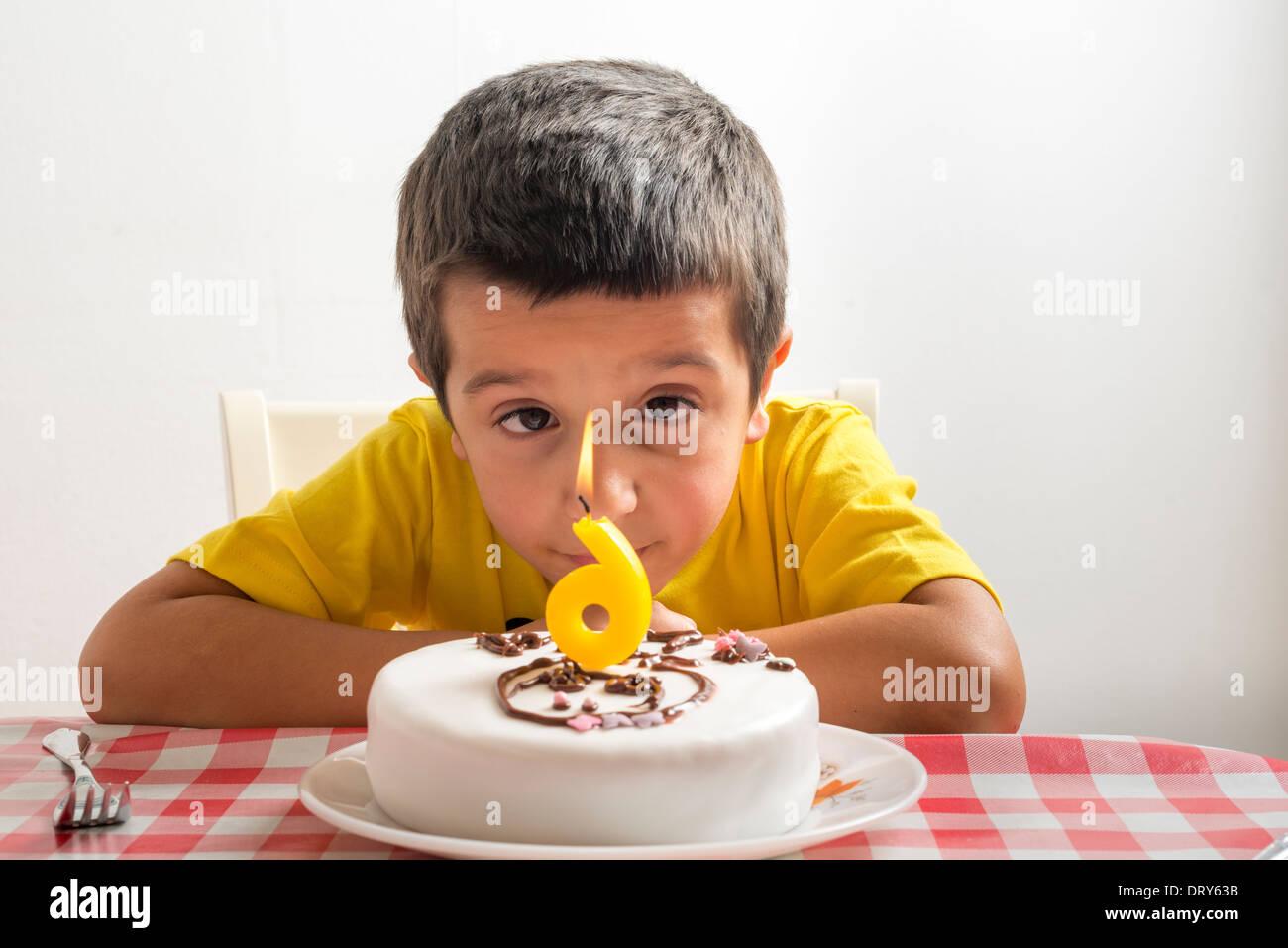 Niño de seis años que estudia el pastel de cumpleaños Imagen De Stock