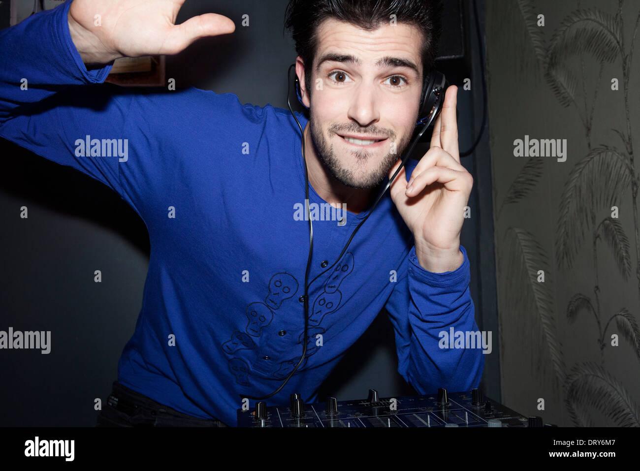 DJ utilizando auriculares de audio y mezclador, Retrato Foto de stock
