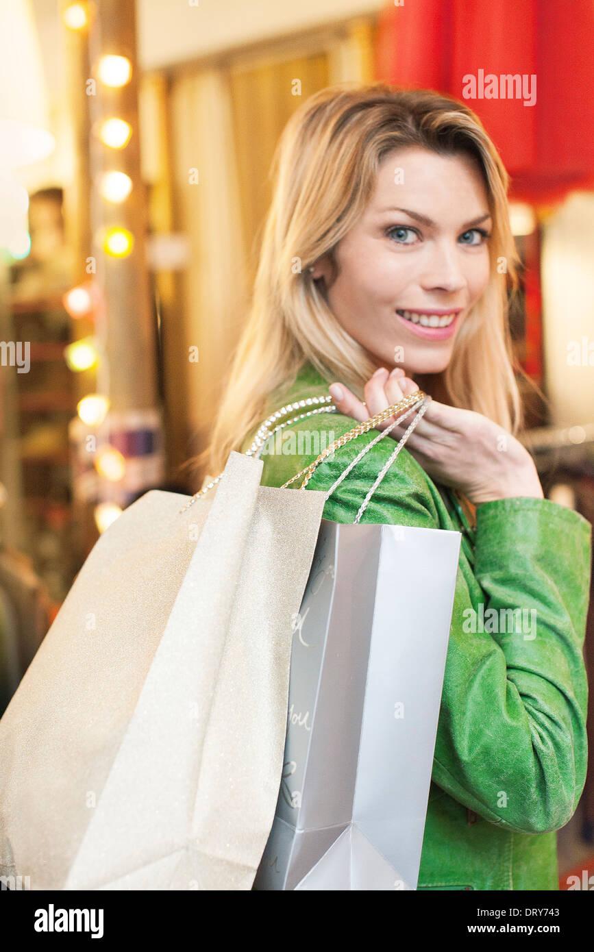 Mujer llevando bolsas de compras sobre el hombro Foto de stock