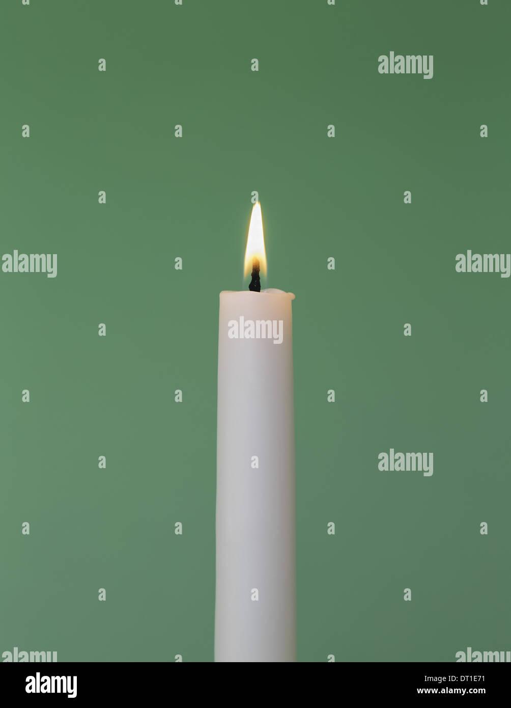 Vela de cera blanca fina con pequeñas llamas encendidas Imagen De Stock