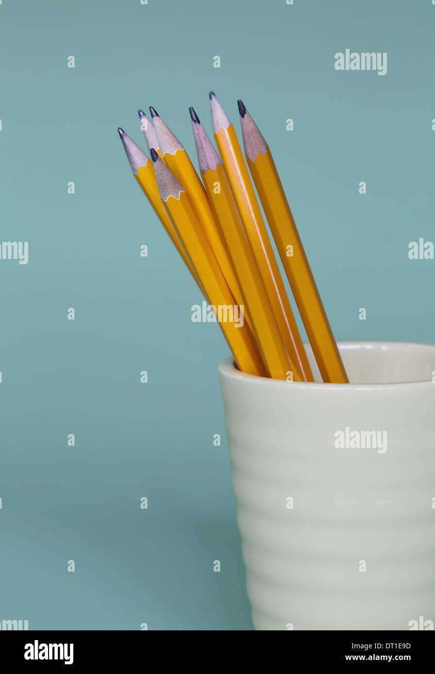 Afilan los lápices en taza sobre fondo azul. Imagen De Stock