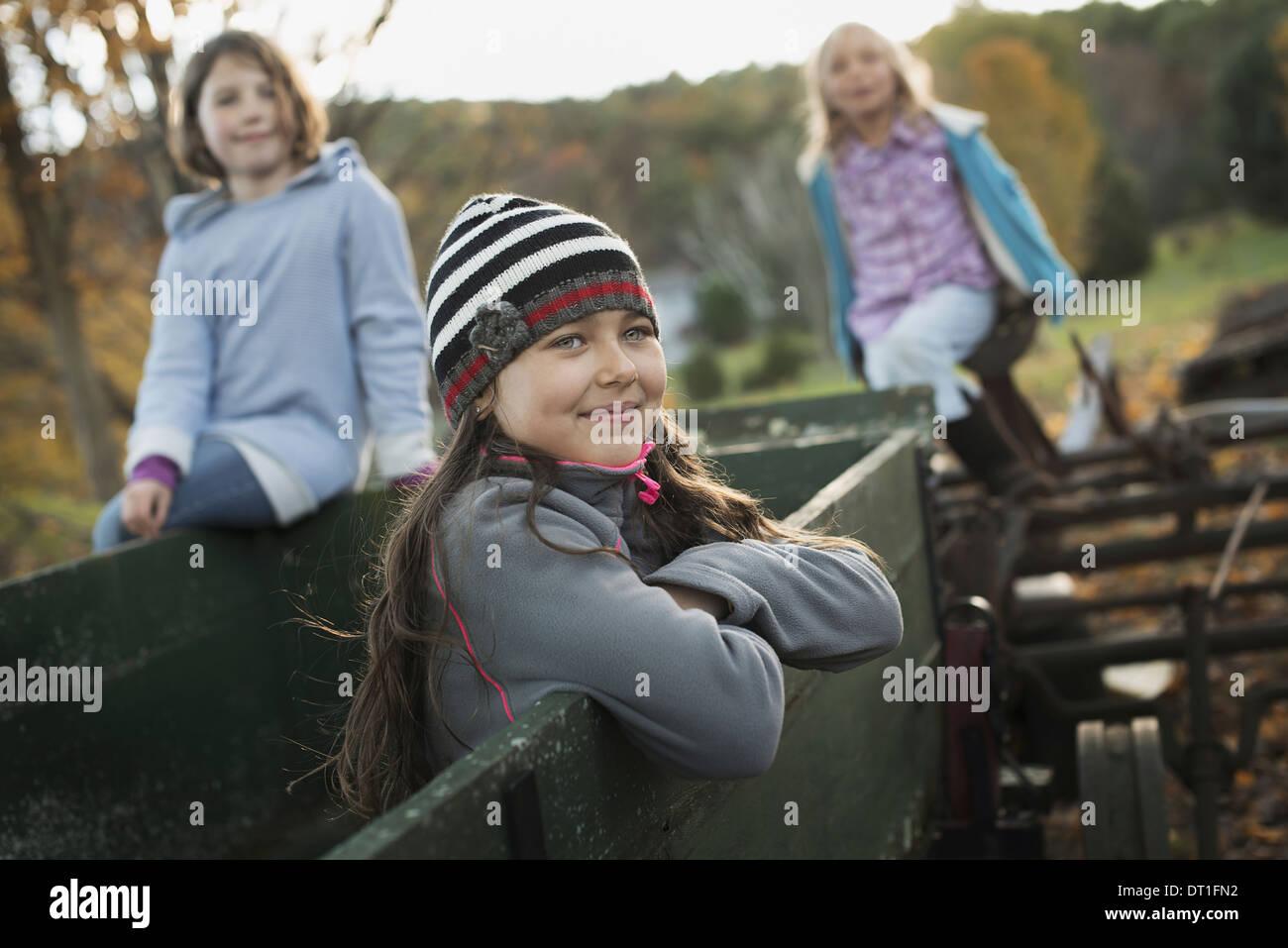 Tres chicas jóvenes en la granja en un viejo remolque Foto de stock