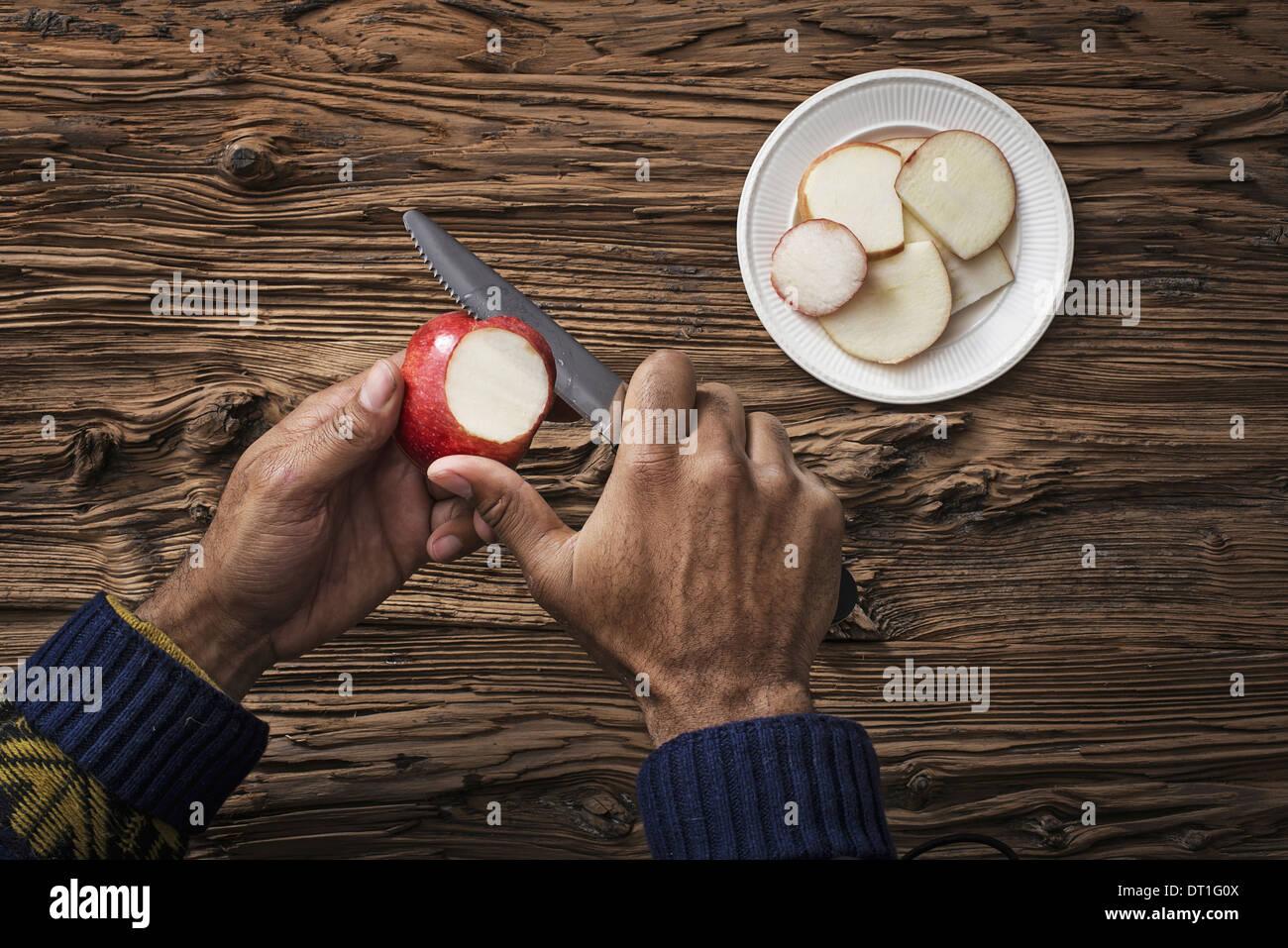 Una persona sosteniendo y cortando secciones de una manzana de piel roja Imagen De Stock