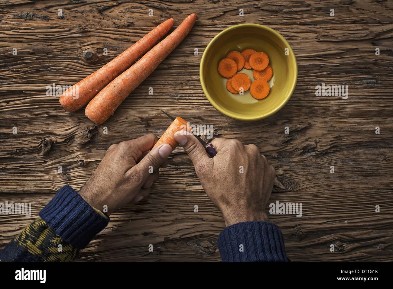 Una persona sosteniendo y cortar en rodajas zanahorias frescas en un recipiente Imagen De Stock