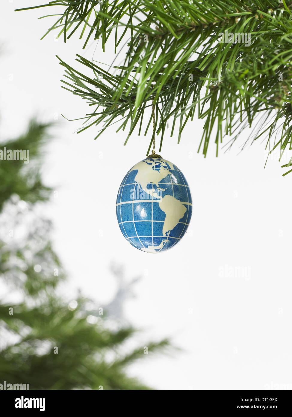 Decoraciones rama de un pino y un adorno azul y blanco un globo con los continentes esbozadas sobre un fondo azul. Imagen De Stock