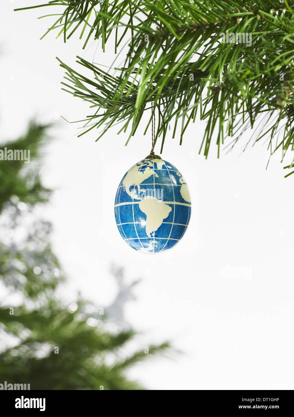 Hoja verde follaje y decoraciones de una rama de árbol de pino y un adorno azul y blanco un globo con los continentes descritos Imagen De Stock