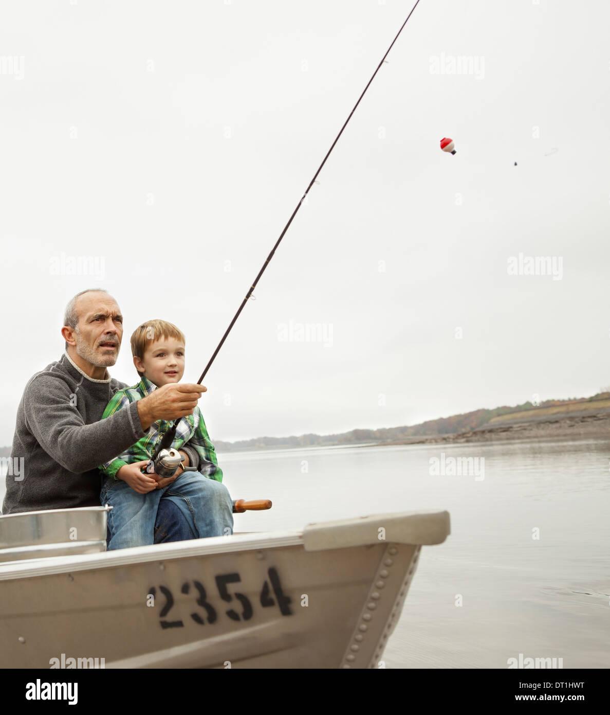 Un día en el lago de Ashokan un hombre mostrando un muchacho cómo pescar sentado en un barco Foto de stock