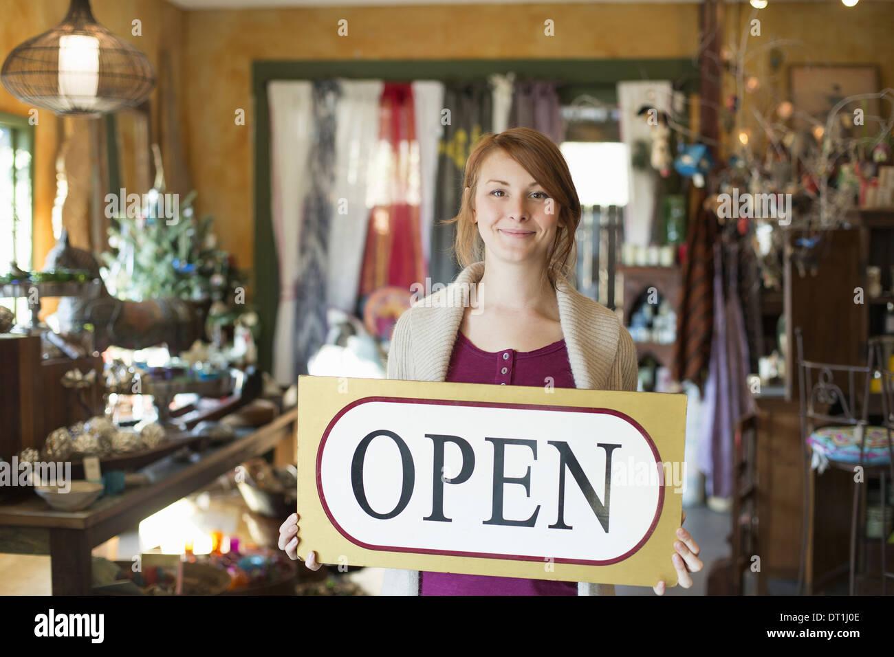 Una mujer de pie en una tienda de antigüedades mantiene abierta una muestra signos de bienes todos a su alrededor. Imagen De Stock