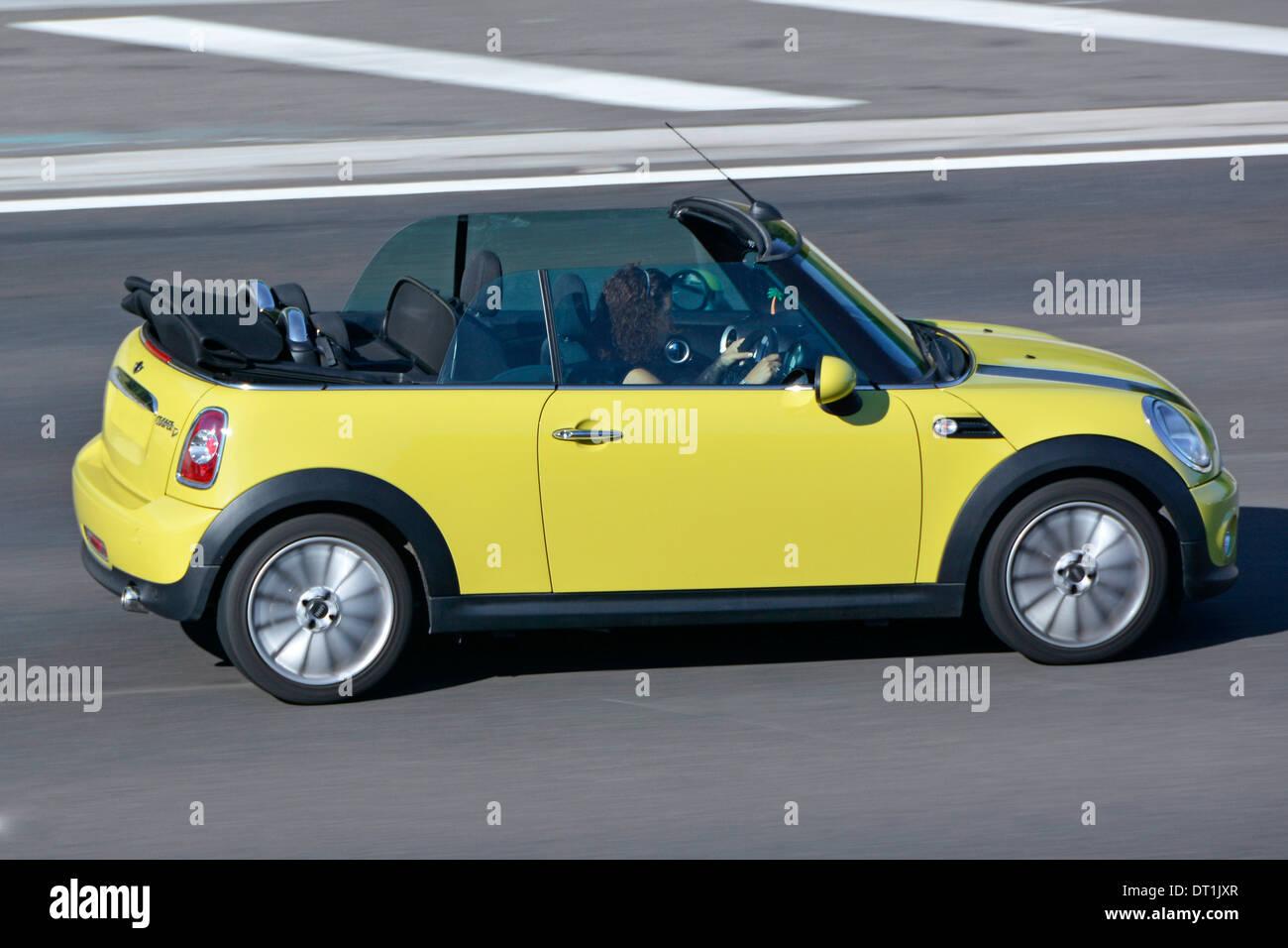 Dos puertas BMW Mini Cooper descapotable coche convertible con la mujer la conducción en autopista autopista M25 Essex, Inglaterra Imagen De Stock
